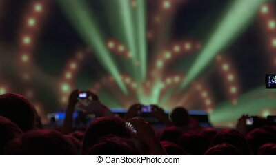 Crowd in front of bright illuminated stage at rock concert