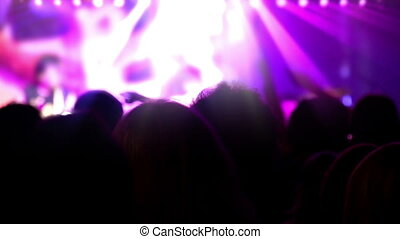 People in the crowd raised their hands in front of the stage. The scene is illuminated by the rays of searchlights