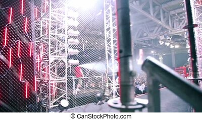 Crowd in large hall on fighting event, guitarist and drummer play, shown in motion from metal constructions