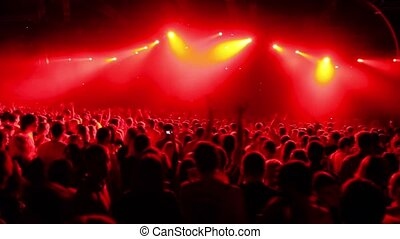 Crowd in large stadium at rave party, view from behind, red...