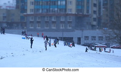 crowd of adults and children sledding snow slide