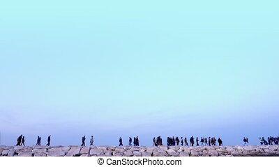 Crowd of different people walk along ancient embankment