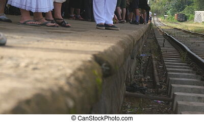 Crowd of passengers waiting for a train arrival on the station at sunny day. Unrecognizable people expecting railway transport on platform. Concept of travel. Low angle view Close up