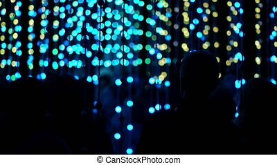 Crowd of People Admiring LED Light Bulbs - Multi colored LED...
