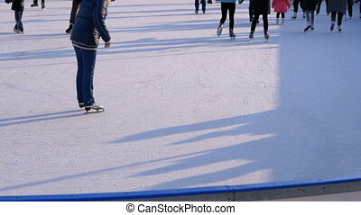 Crowd of People are Skating on Ice Rink in the Sunny Day