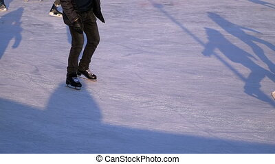 Crowd of People are Skating on Ice Rink in the Sunny Day....
