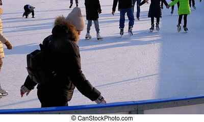Crowd of People are Skating on Ice Rink in the Sunny Day. Slow Motion