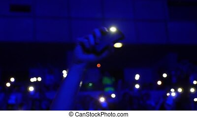 Crowd of people illuminated by colorful light during a concert. 4k