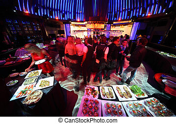 crowd of people relaxing in bar of night club, drinking and...