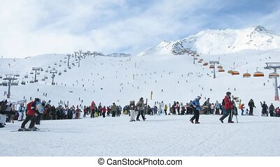 Crowd of people stand and wait turn in a zone of skiing...