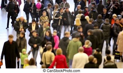 Crowd of people walk around, unfocused view from above