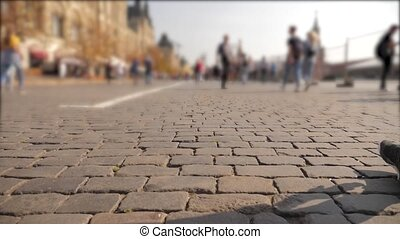 crowd of people walking along a cobblestone pavement to an old blurred background. unknown people go to moscow russia red square. travel around lifestyle Russia concept