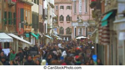 Crowd of people walking along Venetian street