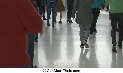 Crowd of people walking indoors,
