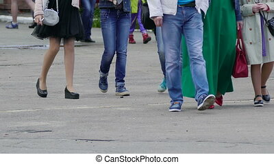 crowd of people walking on the street legs close-up