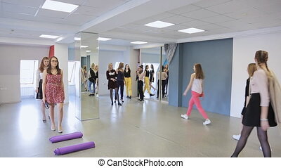 Crowd of pretty females has training in defile in dancing class.