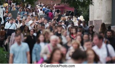 Crowd of unrecognizable people walking along street