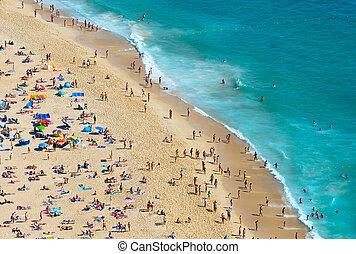 Crowd people ocean beach. Portugal