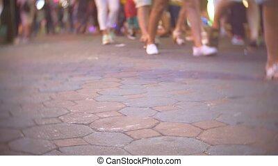 Crowd, walking on streets. Night time. Urban scene. Focus on...