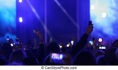 People waving hands with smartphones with flashlight. Live music concert. Big crowd of people dancing on music festival concert at night, street music big event applause raising hands. Handheld video.