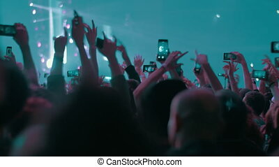 Music fans raising hands and dancing at the concert of favourite singer or band. They trying to capture every moment on mobile