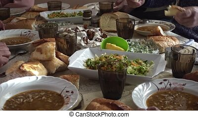 Crowded muslim family eating vegan food and having iftar in ...
