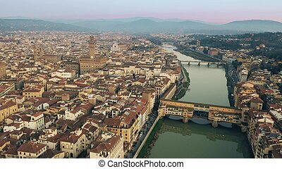 Crowded Ponte Vecchio bridge in the evening, aerial view. Florence, Italy