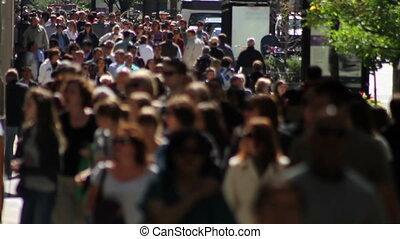 CHICAGO - SEPTEMBER 2011 - A backlit crowd of people walks on a wide sidewalk along Michigan Avenue