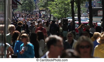 CHICAGO - A backlit crowd of people walks on the sidewalk along Michigan Avenue in slow motion