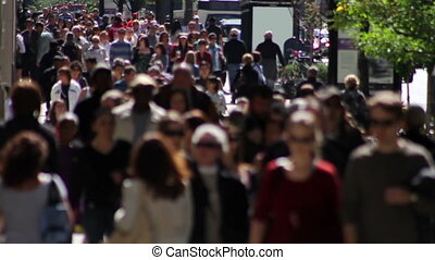 Telephoto shot with a backlit crowd of people on a wide sidewalk, walking in slow motion