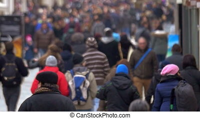 Slow motion shot of people walking along the crowded street in spring or fall. Shot is made with slight defocus.