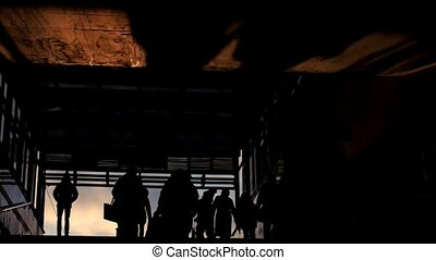 Crowds of people get out from subway at winter sunset, silhouette