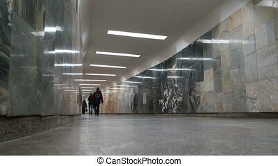 Crowds of people walking by an underground passage, time...