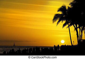 Crowds of tourists gather to watch the sunset on Waikiki Beach Honolulu Oahu Hawaii USA