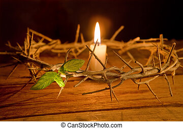 Candle burning in the middle of a crown of thorns at easter