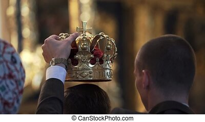 Crowns for wedding in church. Newlyweds at ceremony, priest...
