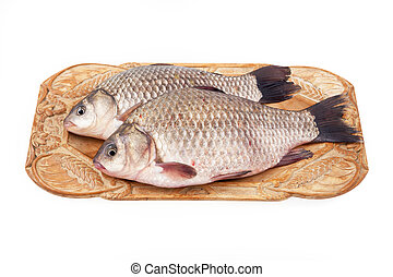Crucian on a plate - Two crucian fish on a wooden plate