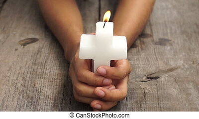 Crucifix candle - A person holding a lit crucifix candle on...