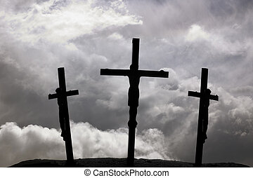 Crucifixion of Jesus on the cross with two crosses beside...