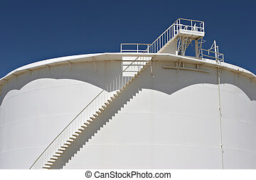 large white oil storage tank outside of town, against a deep blue sky
