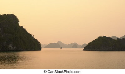 CRUISE BOAT IN HA LONG BAY AT SUNSET, CAT BA NATIONAL PARK,...