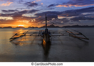 Cruise boat standing still on water with sunset in background, Palawan, Philippines
