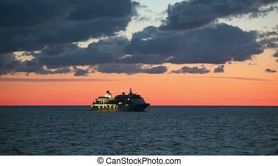 Cruise liner with illumination floats in sea at sunset