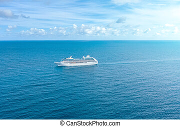 Cruise ship liner sails in the blue sea leaving a plume, seascape. Aerial view The concept of sea travel, cruises.