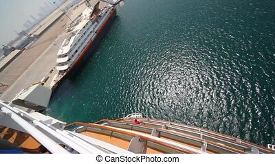 cruise ship moving pass moorage, top view from upper deck in...