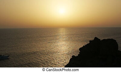 Cruise ship on a clear day with calm seas and sunset sky on the greek island of santorini