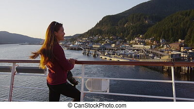 Cruise ship passenger in Alaska city of Ketchikan standing on cruise ship deck while sailing Inside Passage. Ketchikan is a famous Alaska cruise ship destination for tourist travel sightseeing.
