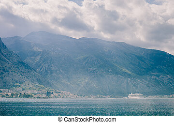 cruise ship sailing in beautiful bay with mountains