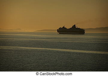 cruise ship at sunset with mountains in background