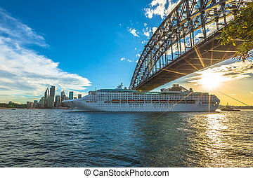 Cruise ship under Sydney Harbour Bridge at sunset with...